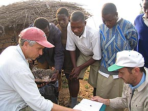 Thomas Smith in the field. Tom Smith (far left) in Uganda doing research on avian blood parasites with Gediminas Valkiunas from the University of Vilnius (right), and residents of the village of Western Uganda near Bwindi Forest National Park. Image credit: University of California