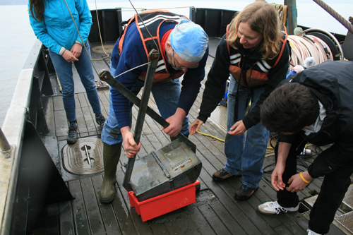 Andrea Ogston (upper right) and students empty sediment into a bucket to study the contents. Image credit: Emily Eidam, UW