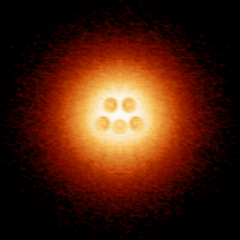 An artificial atomic nucleus made up of five charged calcium dimers is centered in an atomic-collapse electron cloud. (Image courtesy of Michael Crommie)