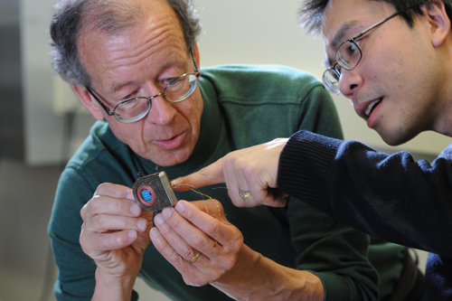 Cortex communication. Engineers Arto Nurmikko and Ming Yin examine their prototype wireless, broadband neural sensing device. Image credit: Fred Field for Brown University