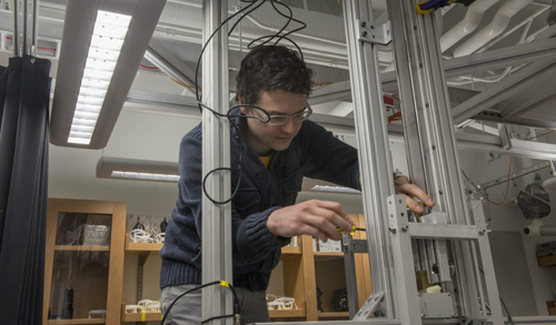 "Dustin Kleckner, postdoctoral scientist at the James Franck Institute, adjusts the experimental apparatus that generates knotted vortices in Prof. William Irvine's laboratory. ""We built several different setups until we found one that works really well,"" Kleckner said. Photo by Robert Kozloff"
