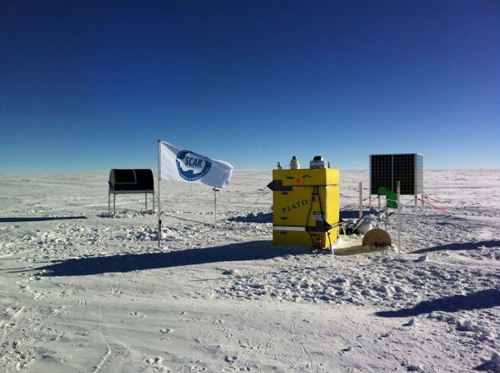 An oddity on a barren snowy plateau, an astronomical observatory watches the skies. From left, the mailbox-like HEAT telescope, the yellow PLATO-R instrument module with cameras and antennas on the rooftop and a cube of solar panels to power the observatory in the summer. (Photo by: Craig Kulesa)