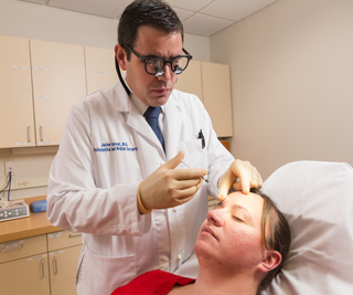 Javier Servat, MD, injects a Botox treatment. Photo by Robert Lisak