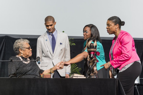 Maya Angelou is presented the gift of a statue by N'Kosi Oates, Brooklynn Hitchens and Kasandra Moye, director of the Center for Black Culture. Photos by Kathy F. Atkinson and Evan Krape