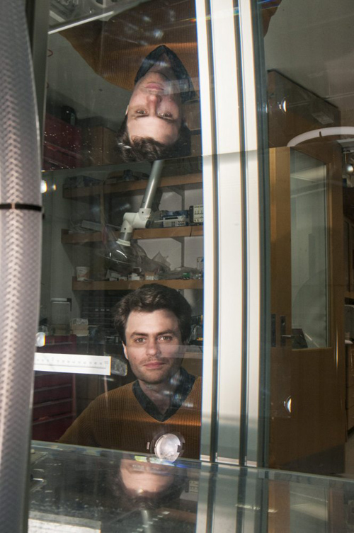 William Irvine, assistant professor in physics, peers through the experimental water tank in his laboratory at the Gordon Center for Integrative Science. Photo by Robert Kozloff