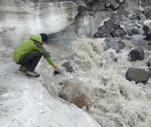 Field assistant Ben Gready measures the electrical conductivity of the 'N' glacier outflow. By making this measurement at different times of the season, scientists can compare concentrations of dissolved nutrients in meltwater passing through the subglacial environment. Early in the melt season, the network of tunnels and chasms under the glacier is less efficient at draining meltwater, extending the meltwater's contact with sediments and bedrock, thus picking up more dissolved nutrients. (Photo by Matt Charette, Woods Hole Oceanographic Institution)
