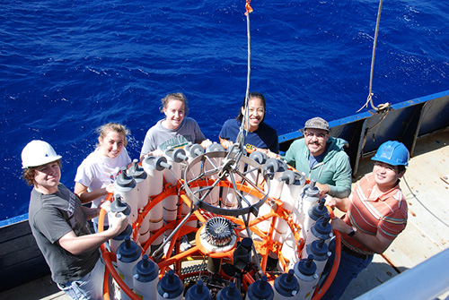 Wang, far right, and his students and lab members (clockwise from far left, Elliott Roberts, Kelly Knorr, Katherine Hoering, Sophie Chu, and Nick Tuttle) at sea around a CTD rosette.  CTDs measure conductivity or salinity, temperature, and depth and are a common tool of oceanographic research. Water samples are collected in each of the rosette's canisters at various depths and then chemically analyzed in the lab. (Photo by Taylor Crockford, Woods Hole Oceanographic Institution)