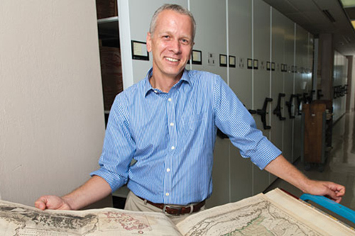 Martin Brückner looks at an atlas in the University of Delaware Library's Special Collections. Photo by Evan Krape