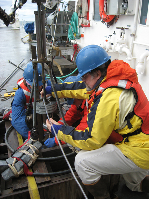 """WHOI researcher Bruce Keafer, right, and colleagues prepare a corer to collect sediment samples from the seafloor. They are part of a survey team assembling a regional distribution map of Alexandrium cysts -- the """"seeds"""" or dormant cells of the algae responsible for producing the PSP toxin. The team will analyze the samples to determine the abundance of Alexandrium cysts and, with the help of computer models that simulate different scenarios of weather and oceanographic conditions, develop a forecast of the overall regional abundance of toxic cells expected in 2013. (Photo by Amy Lloyd-Rippe)"""