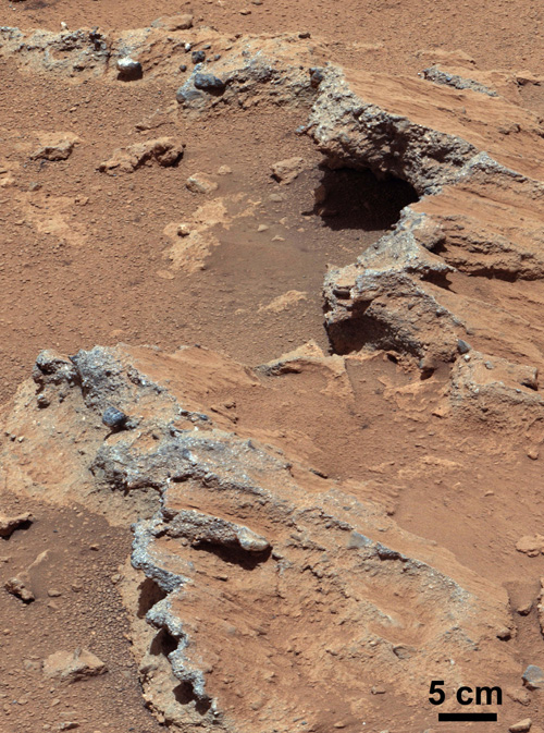 "NASA's Curiosity rover found evidence for an ancient, flowing stream on Mars at a few sites, including the rock outcrop pictured here, which the science team has named ""Hottah"" after Hottah Lake in Canada's Northwest Territories. It may look like a broken sidewalk, but this geological feature on Mars is actually exposed bedrock made up of smaller fragments cemented together, or what geologists call a sedimentary conglomerate. Scientists theorize that the bedrock was disrupted in the past, giving it the titled angle, most likely via impacts from meteorites. Image credit: NASA/JPL-Caltech/MSSS"