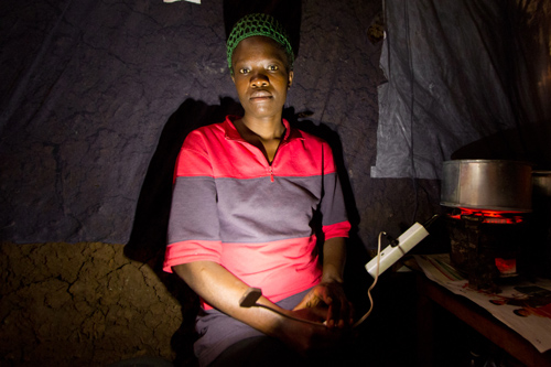A woman in Kibera, the largest slum in Nairobi, tries out an early version of the VOTO charger. (Kenya photos courtesy of Jacobson)