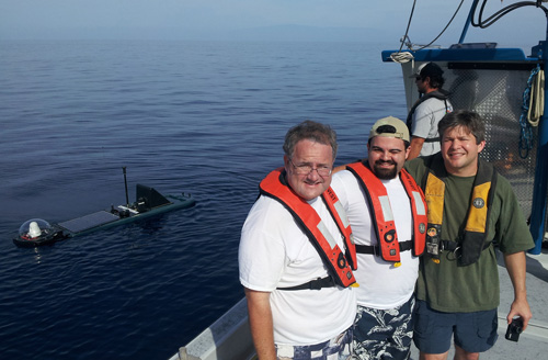 GTRI researchers (l-r) Jim Maloney, Matthew Habib and Gregory Kiesel pose with a Wave Glider autonomous marine robot during tests in the ocean off Hawaii. Image credit: Georgia Tech Research Institute (GTRI)