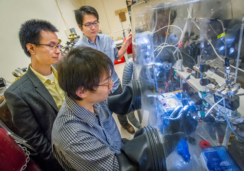 Peidong Yang (left), Hao Ming Chen and Chong Liu (glove box) have developed the first fully integrated nanoscale artificial photosynthesis system. (Photo by Roy Kaltschmidt)