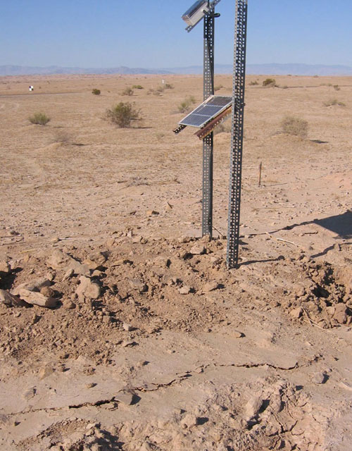 A solar-powered creepmeter beside cracks generated by a creep event on California's Superstition Hills Fault in 2006. Creep events are slow and silent, last hours, and can accommodate approximately 3 centimeters of slip per event. (Photo courtesy of Matt Wei)
