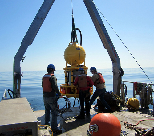 The ESP, shown here being deployed from the WHOI ship R/V Tioga, uses a robotic mechanism to carry out analyses, thereby eliminating the strict requirement for sending people to the sea to collect samples and process them manually. (Photo by Isaac Rosenthal, Woods Hole Oceanographic Institution & Northeastern University