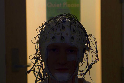 Cap of Sensors. In a sleep lab on Brown's campus researchers use now using caps of EEG sensors in studies of how the brain works to consolidate learning visual tasks. Here graduate student Aaron Berard models the cap. Image credit: Brown University