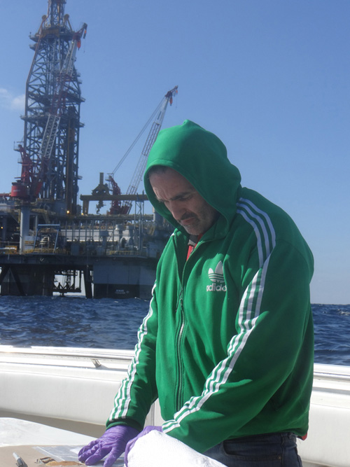 The research team's second sampling expedition in December 2012, was more challenging due to the close proximity of a BP survey vessel, Olympic Triton, which was operating two ROVs, and a mobile offshore deep drilling unit. The rig and vessel each require a reasonable stand-off distance for safety precautions. WHOI's Chris Reddy is shown here, with the drilling rig behind him. (Photo by Bob Nelson, Woods Hole Oceanographic Institution)