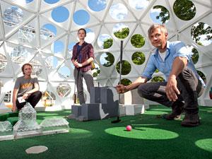 "Professor Chris Larson, with students Jordan Rosenow (left) and Sara Nichol (center) in their sculpture, ""Mega Golf."" Image credit: University of Minnesota"