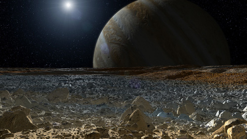 This artist's concept shows a simulated view from the surface of Jupiter's moon Europa. Europa's potentially rough, icy surface, tinged with reddish areas that scientists hope to learn more about, can be seen in the foreground. The giant planet Jupiter looms over the horizon. Image credit: NASA/JPL-Caltech