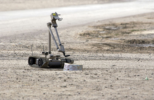 A United States Army explosive ordnance disposal robot pulls the wire of a suspected improvised explosive device in Iraq. Image credit: U.S. Navy photo by Journalist 1st Class Jeremy L. Wood. (Image source: Wikipedia)