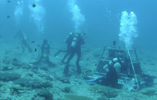 Glenn McDonnald, Scott Gallager, and Amber York of WHOI and Koichi Toda of OIST installing the OceanCube central node in waters off Okinawa, Japan. (Photo courtesy of OIST)