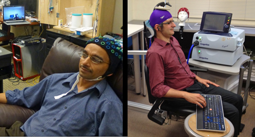 """University of Washington researcher Rajesh Rao, left, plays a computer game with his mind. Across campus, researcher Andrea Stocco, right, wears a magnetic stimulation coil over the left motor cortex region of his brain. Stocco's right index finger moved involuntarily to hit the """"fire"""" button as part of the first human brain-to-brain interface demonstration. Image credit: University of Washington"""