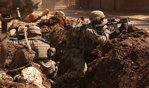 Sgt. Auralie Suarez and Private Brett Mansink take cover during a firefight with guerrilla forces in the Al Doura section of Baghdad on the 7th of March. The soldiers are from Company C, 5th Battalion, 20th Infantry Regiment, 3rd Brigade Combat Team, 2nd Infantry Division. Author: Sean A. Foley (Image source: Wikipedia)