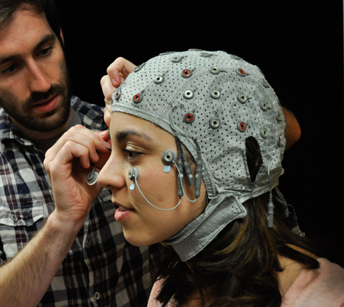 A look inside the mind: Davi Vitela dons a cap used to take EEG scans of her brain activity while she views a series of images. Jay Sanguinetti's study indicates that our minds perceive objects in everyday life of which we are never consciously aware. (Photo by Patrick McArdle/UANews)