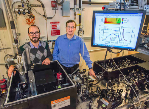 """Giacomo Coslovich (left) and Robert Kaindl (right) next to the laser setup that generates extremely short pulses of light at """"mid-infrared"""" wavelengths, far beyond the spectrum perceptible by the human eye. Image credit: Berkeley Lab"""