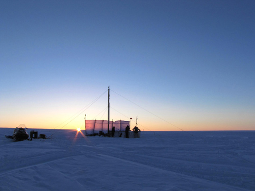 Drill rig used to extract firn cores from within the Greenland firn aquifer. One of the snowmobiles used in the 300 km traverse of the ice sheet to reach the drill site. Pictured, Clément Miège (co-author and PhD student University of Utah), and Terry Gacke (Ice Drilling Design and Operations). Photo Credit: Evan Burgess