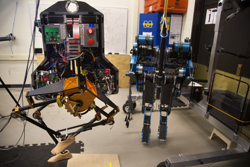 MARLO, a bipedal robot, next to its predecessor, MABEL, in a lab located in the Environmental and Water Resources Engineering Building on November 19, 2013. MARLO is the successor in EECS Professor Jessy W. Grizzle's research group to MABEL, another bipedal robot that is being retired to be displayed in the Chicago Field Museum. Buss and members of Grizzle's research group test the robot, making minute adjustments to improve its ability to walk in hopes of having applications in human prosthetics and the general robotics community. Image credit: Joseph Xu, Michigan Engineering Communications & Marketing