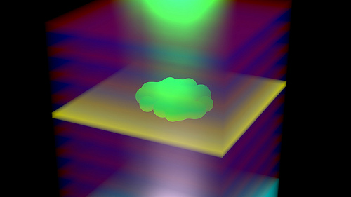 Polariton BEC within the polymer-filled micro-resonator consisting of the luminescent polymer layer (yellow) and the two mirrors each consisting of many pairs of different transparent oxide layers (red and blue). The polaritons are created by excitation of the polymer layer from below with a laser beam (white). The polaritons (green), which are bosons composed of photons and electron-hole pairs, are formed through interactions of the polymer with the microcavity. Once a critical density is reached, the polaritons undergo Bose-Einstein condensation, emitting green laser-like light through the top mirror. Photo Credit: IBM Research