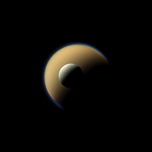 Saturn's largest and second largest moons, Titan and Rhea, appear to be stacked on top of each other in this true-color scene from NASA's Cassini spacecraft. Image Credit: NASA/JPL-Caltech/Space Science Institute