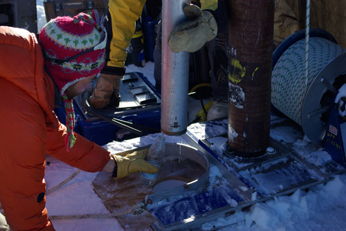 Water from the Greenland perennial firn aquifer draining from a core extracted 12 m below the surface of the ice sheet. The core was drilled in April, months prior to seasonal melt, with air temperatures -15 C confirming the water was retained at depth throughout the winter. Clément Miège is pictured collecting a sample of the water. Photo Credit: Ludovic Brucker