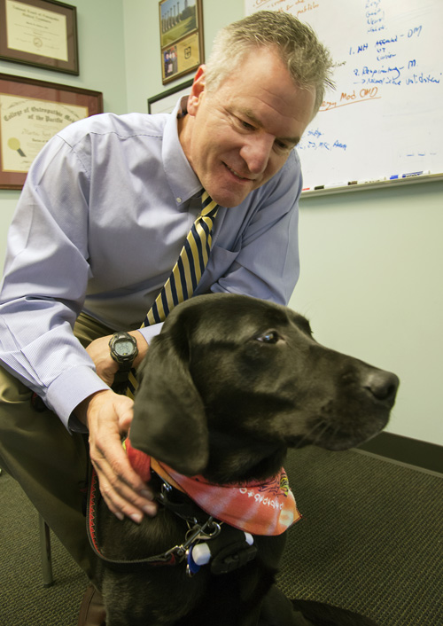 Gene therapy researcher Martin K. Childers with his family dog, Bella, who carries the gene for the disorder he studies. Image credit: Clare McLean