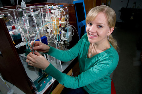"""Chemical oceanographer Katie Shamberger, shown here with an instrument in co-author Dan McCorkle's lab that measures seawater CO2 parameters, led the water sampling effort in Palau in the western Pacific. There, the scientists studied nine sites along a transect that stretched from the open ocean, across the barrier reef, into the lagoon and then into the bays and inlets around the Rock Islands of Palau.  """"When we first plotted up those data, we were shocked""""  that the water in the Rock Islands was at levels of acidification that are expected for the open ocean in the tropical western Pacific by the end of the century. (Photo by Tom Kleindinst, Woods Hole Oceanographic Institution)"""