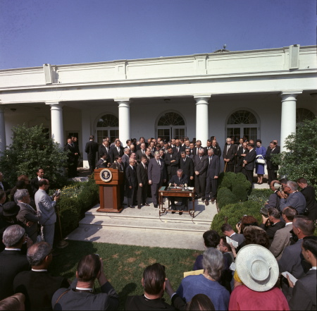 President Johnson signing the Economic Opportunity Act of 1964. Image credit: Wikipedia