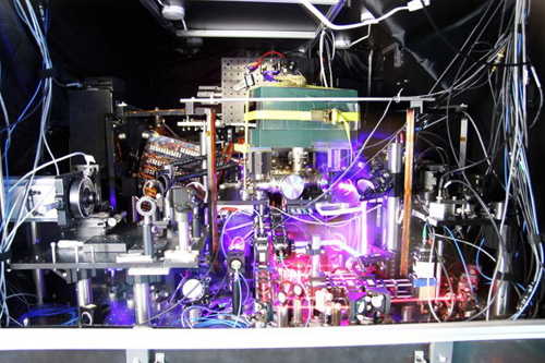 JILA's experimental atomic clock based on strontium atoms held in a lattice of laser light is the world's most precise and stable atomic clock. This image is a composite of many photos taken with long exposure times and other techniques to make the lasers more visible. (Image credit: Ye group and Brad Baxley/JILA)