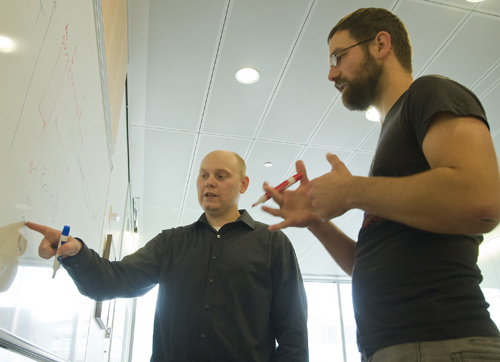 Population geneticists Joshua Akey (left) and Benjamin Vernot of the UW Department of Genome Sciences (right) discuss models of human evolution. Image credit: Clare McLean