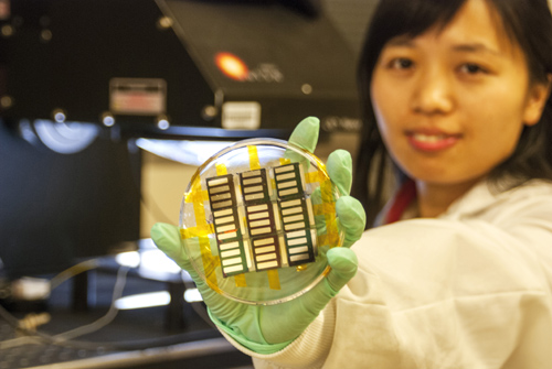 UCLA postdoctoral researcher Huanping Zhou displays perovskite solar cells made using a vapor-assisted solution process. The process has shown potential for inexpensive manufacturing of high-efficiency solar cells. Image credit: University of California