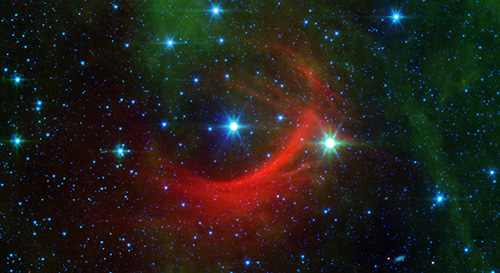 The red arc in this infrared image from NASA's Spitzer Space Telescope is a giant shock wave, created by a speeding star known as Kappa Cassiopeiae. Image credit: NASA/JPL-Caltech