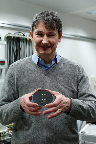 Thomas Toifl, high-speed CMOS serial link circuit design scientist at IBM Research - Zurich holding a silicon wafer with eight prototypes of the new 90GS/s 8b 667mW 64× Interleaved SAR ADC in 32nm Digital SOI CMOS. Image credit: IBM Research