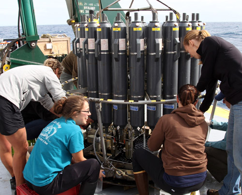 UW graduate student Katherine Heal (far right) attaches a water collection bottle to an oceanographic instrument that will be lowered in water off Washington's coast. Image credit: Chris Tuck, UW