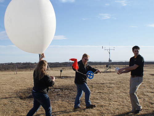 Katie Crandall, doctoral candidate in atmospheric science, Patrick Market, professor of atmospheric sciences, and Josh Kastman, doctoral candidate in atmospheric science, prepare to launch a weather balloon. These balloons carry data-collecting devices that pass through elevated convection events in the atmosphere, radioing back data that will provide clues as to why this phenomenon triggers heavy rain-producing thunderstorms. Image credit: University of Missouri