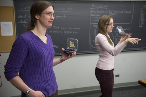 UChicago PhD candidates Samantha Stam, in biophysics (left), and Lisa Nash, in physics, work with high school students during a workshop of the Midwest Conference for Undergraduate Women in Physics last month. In this workshop, Stam and Nash demonstrated how to use berries as a source of energy to turn on a light bulb. Photo by Robert Kozloff