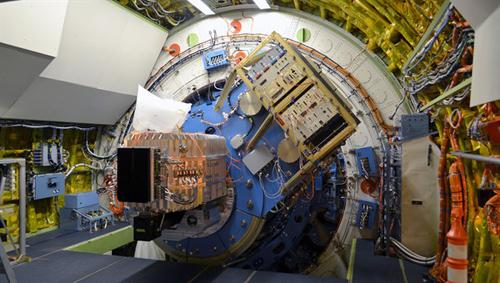 """Das Bild zeigt den rechteckigen, silbern glänzenden Aluminium-Kryostaten des FIFI-LS-Instruments, der an die blaue Tragestruktur des Teleskops montiert ist. Der Cryostat ist mit flüssigem Stickstoff und flüssigem Helium gefüllt, um die optischen Elemente und Detektoren auf die notwendigen tiefen Temperaturen zu kühlen. Die dunklen Kästen vor und unterhalb des Kryostaten enthalten ebenso wie das schräg oberhalb angeordnete """"Instrument-Rack"""" die Elektronikboxen zur Steuerung und Datenverarbeitung von FIFI-LS. Image credit: DSI."""