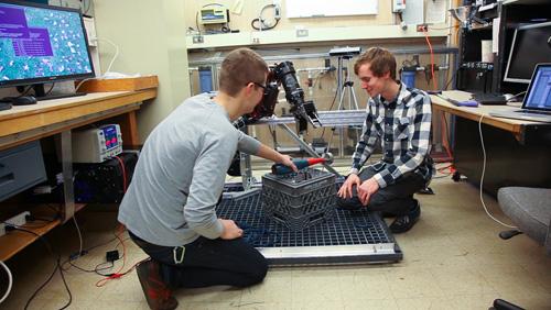 Undergraduates students Derek Martin, left, and Ryan Cox work on instrumentation with the BluHaptics team. Image credit: Conrado Tapado, UW