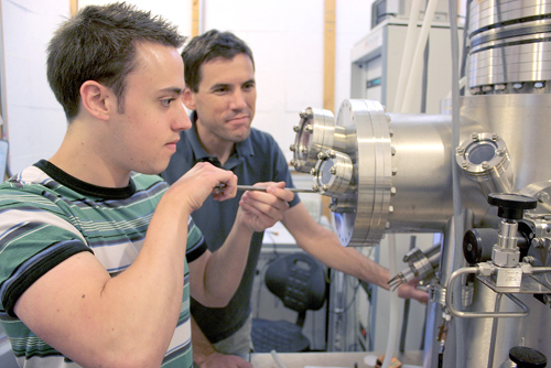 Brian LeRoy, UA associate professor of physics (right) and graduate student and first author of the study, Matthew Yankowitz, use a tunneling electron microscope to probe the electronic properties of graphene. (Photo by: Daniel Stolte/UANews)