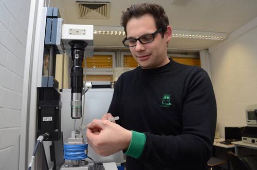 Diplom-Nanowissenschaftler Dennis Holzinger bereitet einen Versuch mit dem neuartigen Analysechip vor. Er platziert ihn auf den Träger eines Elektromagneten, der das magnetische Kraftfeld zur Steuerung der zu untersuchenden Flüssigkeit auf dem Chip aufbaut. Mit einem Mikroskop (Mitte) kann Holzinger den Verlauf des Versuchs beobachten. Foto credit: Dilling/Uni Kassel.