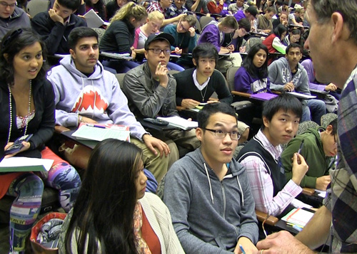 Freeman heads into the auditorium to help as students huddle trying to reason out an answer to a genetics question. Image credit: U of Washington